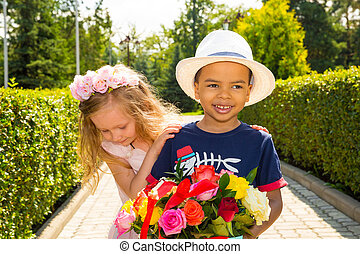 Black african american boy kid gives flowers to girl child on birthday. Little adorable children in park. Childhood and love.