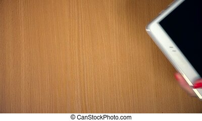 Hang plug micro USB wire into white tablet computer on wooden background