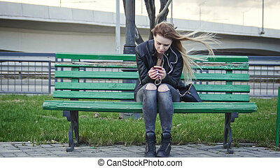 Dissapointed girl with long blonde hair in leather jacket...