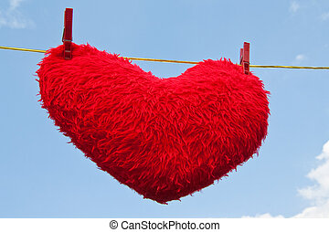 Heart on a clothesline - Heart-shaped red plush pillos on a...