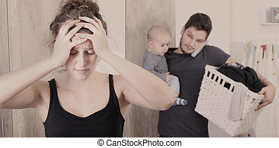 Young mother suffering from postpartum depression - Husband...