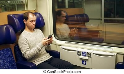 Serious caucasian man typing email in his mobile phone in a...