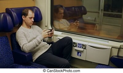 Man watching movie in his smartphone in a train. 4K video -...