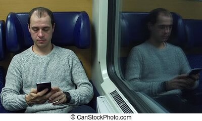Happy man taking his seat in a train and sending messages in...
