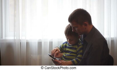 father and son are sitting with the phone near window