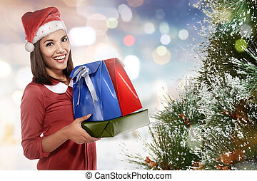 Pretty asian woman in santa hat with many gift boxes
