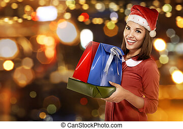 Smiling asian woman in santa hat with many gift boxes