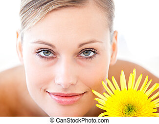 Close-up of a radiant woman lying on a massage table with a flower in a health spa