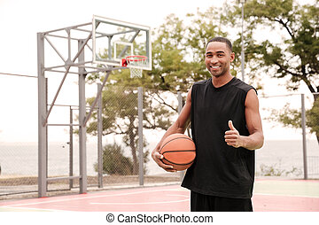 Happy basketball player making thumbs up gesture - Image of...