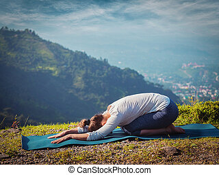 Sporty fit woman practices yoga asana Balasana - child pose...