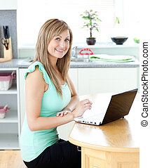 Delighted blond woman using her laptop smiling at the camera...