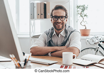 Great working day! Handsome young man looking at camera and smiling while sitting on working place in creative office