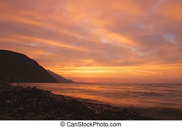 the sunrise at Lake Baikal in summer with orange background...