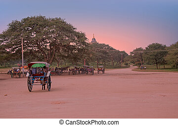 Horse carts on a dusty road in the temple area in Bagan...