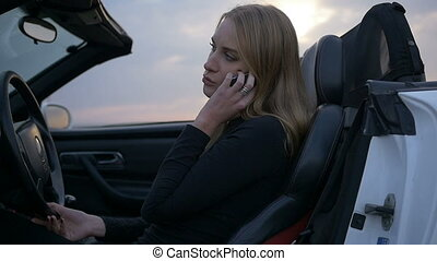 The woman driving the car talking on the phone.