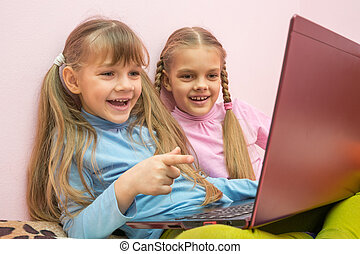 Two girls looking at a laptop and laughing merrily, one is...