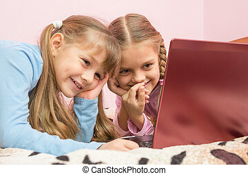 Sisters watching a cartoon on a laptop and laughing at a...