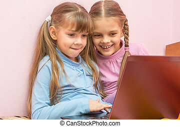 Two girls playing in a notebook fun laughing