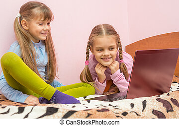 Two girls looking at a laptop and laughing together having...