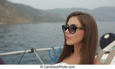 Gorgeous green-eyed brunette in sunglasses has a rest on a yacht at sea
