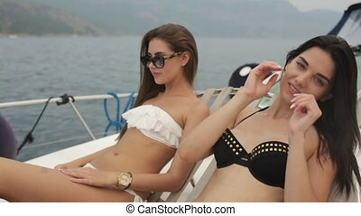 Two chic girls in bikinis lying on a yacht