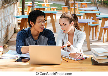 Happy young couple of students using laptop at the table -...