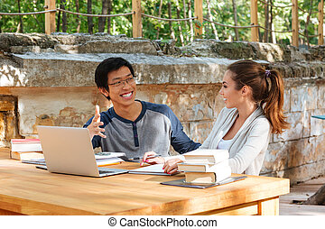 Happy young couple of students studying with laptop in cafe...
