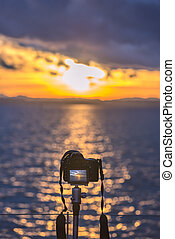 Camera on a tripod capturing the sunset - Colorful image...