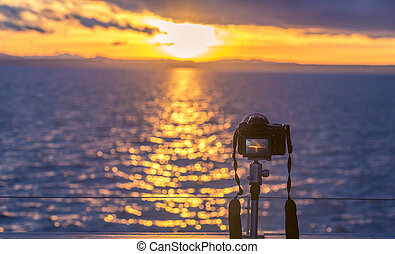 Sunset over water and a DSLR camera - A high-performance...