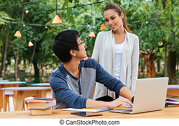 Couple talking and using laptop outdoors - Smiling young...