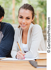 Smiling attractive young woman sitting and writing at the...