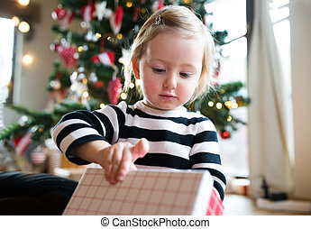 Little girl at the Christmas tree opening present -...