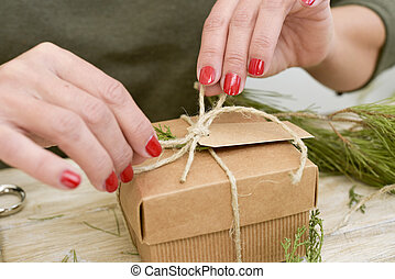 woman tying a string around a gift - closeup of a young...