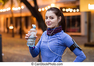 Young runner resting, drinking water in illuminated night...