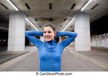 Young runner under the bridge in the evening stretching arms...