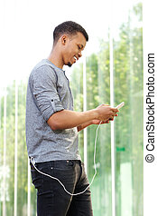 smiling man standing and using smart phone outside
