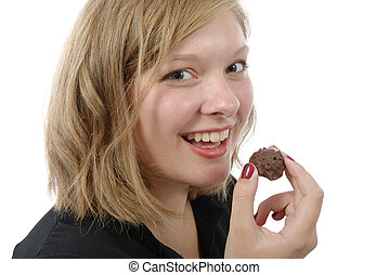 smiling young woman eating a chocolate candy