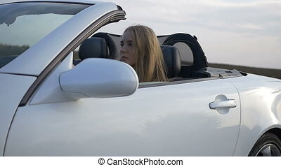 Girl rides a white convertible.