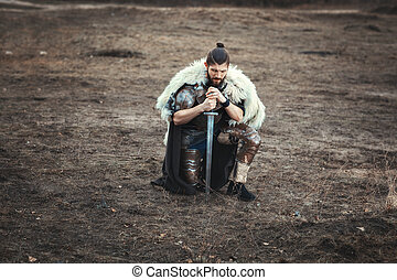 Formidable man with a sword in field sad. - Formidable man...