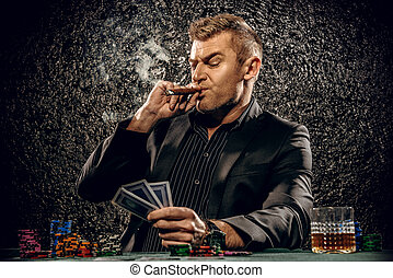 poker game - Rich gambler man with the cards and chips in...