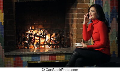 Beautiful woman sits near fireplace, talks on mobile phone....