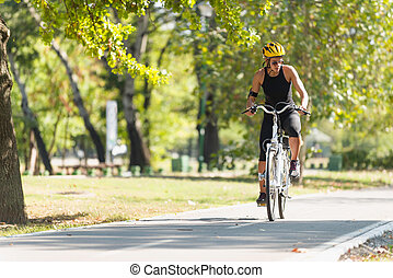 Riding e-bike - Young woman riding electric bicycle or...
