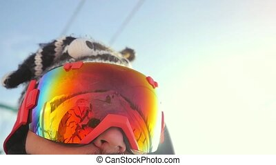 Skier in glasses skiing downhill in high mountains on ski lift during sunny day in slow motion. 1920x1080