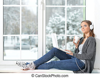 Woman with laptop on windowsill - Beautiful young woman in...
