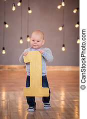 Little boy stands behind number one year
