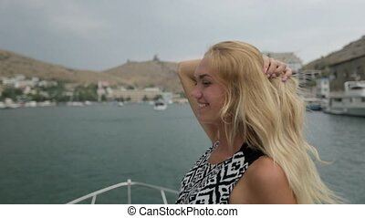 Happy blond woman on the moving motor boat in the sea