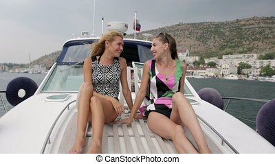 Beautiful girls sitting on the motorboat in the sea and...