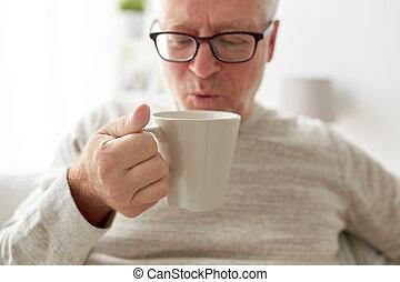 happy senior man drinking tea or coffee at home