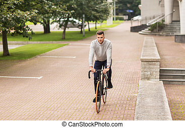 young man riding bicycle on city street - lifestyle,...