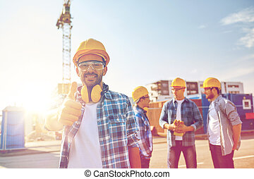 builders showing thumbs up at construction site